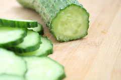 Cucumber slice. Cucumber and slices isolated over wood background Royalty Free Stock Images