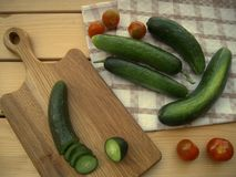Cucumber sliced on a cutting board and other on a kitchen towel and cherri tomatoes. Ripe cucumbers, juicy, cherry tomatoes, on a rustic table, prepared for Royalty Free Stock Photo