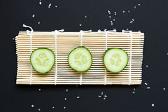 Cucumber slices on the bamboo mat on black background Royalty Free Stock Images