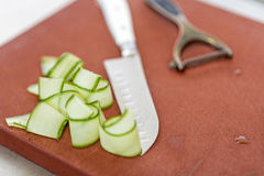 Cucumber slices with nife. Thin and long cucumber slices with nife and peeling knife on cutting board Stock Image