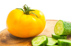 Cucumber with slices and tomato on cutting board Stock Photo