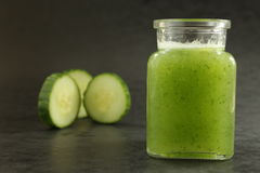 Cucumber smoothie. With three slices cucumber on the dark wallpaper royalty free stock photo