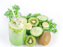 Cucumber smoothies in the bottle, kiwi, parsley, and banana on white wooden table. Royalty Free Stock Photography