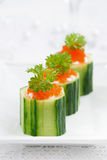 Cucumber tartlets with cream cheese and red caviar, vertical Royalty Free Stock Photo