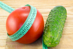 Cucumber and tomato with measuring. Tape over desk - the concept of dieting and health stock images