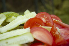 Cucumber and tomato salads. Close-up photo of cucumber and tomato salads in nature background Royalty Free Stock Photography