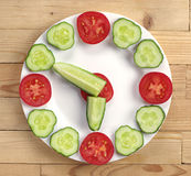 Cucumber and tomato in the shape of clock Stock Photography