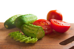 Cucumber and tomato slices on a cutting board Royalty Free Stock Photo