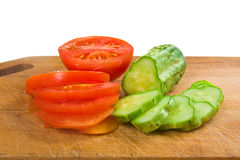 Cucumber and tomato slices on a cutting board Royalty Free Stock Images