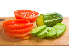 Cucumber and tomato slices on a cutting board Stock Photography