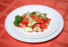 Cucumber tomatoe appetizing vegetable salad. On a red table-cloth Stock Photos