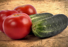 Cucumber and tomatoes closeup on a wooden background Royalty Free Stock Photo
