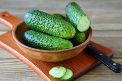 Cucumbers in a bowl on cutting board Royalty Free Stock Photos