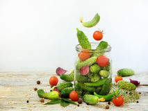 Cucumbers and cherry tomatoes with herbs and spices for pickling in glass jar with flying ingredients Stock Photography