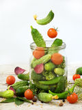 Cucumbers and cherry tomatoes with herbs and spices for pickling in glass jar with flying ingredients Stock Photo