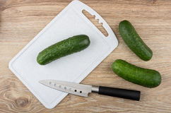 Cucumbers, cutting board and kitchen knife on wooden table Stock Photos