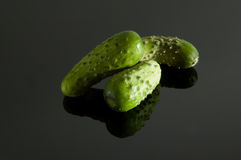 Cucumbers on a gray background. Three cucumbers on a gray reflective background stock photo
