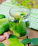 Cucumbers in a jar with leaves and napkin Stock Images