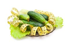 Cucumbers with a measuring tape Royalty Free Stock Photos