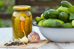 Cucumbers in metal bowl, spices for pickling and jar pickled cucumbers on table Royalty Free Stock Photography