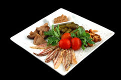 Cucumbers with mushrooms tomatoes and meat. On a square dish cut out on a black background stock photo