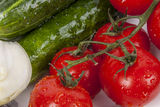 Cucumbers, onion and red tomatos on white plate. Royalty Free Stock Photo