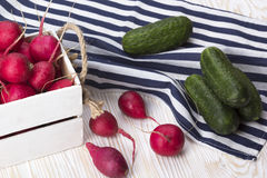 Cucumbers and red radishes in a wooden box. Stock Photo