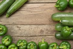 Cucumbers and sweet pepper on wooden table. For background royalty free stock photography