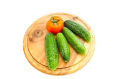 Cucumbers and tomato on cutting board Stock Photos