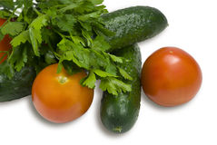 Cucumbers and tomatoes. Green cucumbers and red tomatoes on a white background. Parsley from above lays Stock Photo