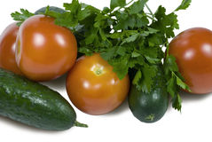 Cucumbers and tomatoes. Green cucumbers and red tomatoes on a white background. Parsley from above lays Stock Photos