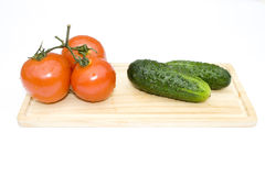 Cucumbers and tomatoes. Disposed on piece of wood isolated on white Royalty Free Stock Image