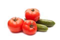 Cucumbers and tomatoes. Fresh cucumbers and tomatoes on white background Royalty Free Stock Image
