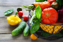 Cucumbers with tomatoes in a basket Stock Images