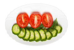 Cucumbers and tomatoes, chopped slices on plate Stock Images