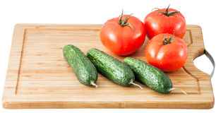 Cucumbers and tomatoes on a cutting board Royalty Free Stock Images