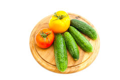 Cucumbers and tomatoes on cutting board Royalty Free Stock Photo