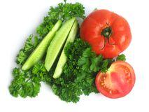 Cucumbers, tomatoes and greens Stock Images