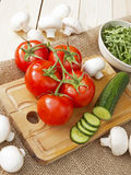 Cucumbers, tomatoes, mushrooms and arugula. On a wooden Board Stock Photo