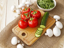 Cucumbers, tomatoes, mushrooms and arugula. On a wooden Board Royalty Free Stock Photos