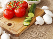 Cucumbers, tomatoes, mushrooms and arugula. On a wooden Board Stock Photography