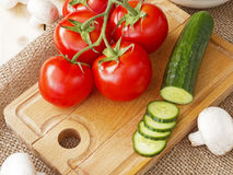 Cucumbers, tomatoes, mushrooms and arugula. On a wooden Board Royalty Free Stock Photo