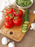 Cucumbers, tomatoes, mushrooms and arugula. On a wooden Board Stock Photos