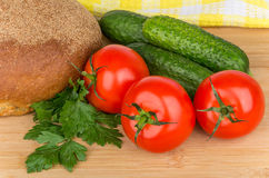 Cucumbers, tomatoes, parsley and bread on board Stock Image