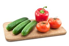 Cucumbers, tomatoes and peppers on wooden board Royalty Free Stock Photo