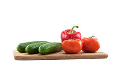 Cucumbers, tomatoes and peppers on wooden board. Isolated on white background Royalty Free Stock Photos