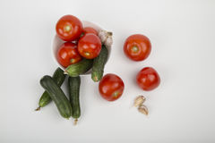 Cucumbers and  tomatoes. Cucumbers and ripe tomatoes on white background Royalty Free Stock Photo