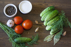Cucumbers, tomatoes and spices. Cucumbers, tomatoes, spices and herbs on a wooden board royalty free stock photography
