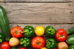 Cucumbers, tomatoes and sweet pepper on wooden table. For background royalty free stock photo