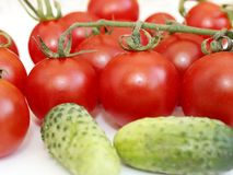 Cucumbers and tomatoes on white plate. Crop of vegetables Stock Image